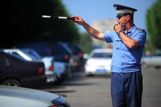 инспектор ГАИ останавливает нарушителя за неуплату штрафа ГИБДД