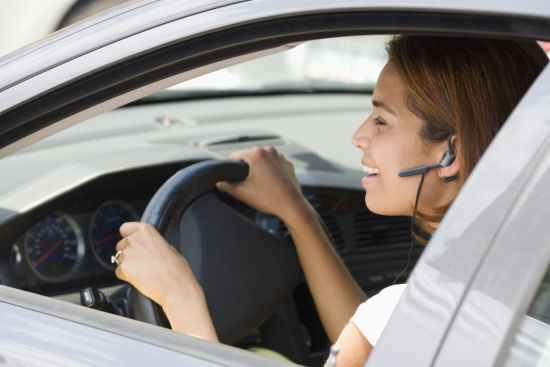 Девушка говорит за рулем по телефону во время движения авто