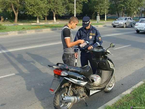 инспектор ГИБДД выписывает штраф за езду на мопеде без прав