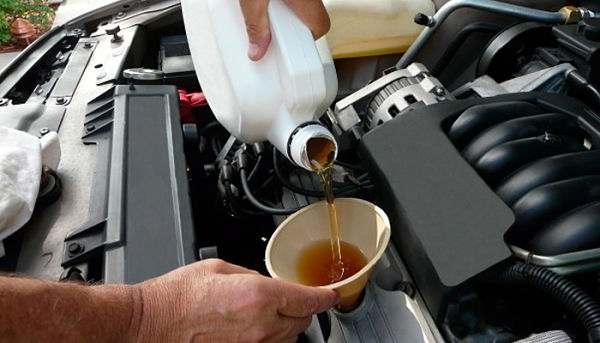 мужчина меняет масло в двигателе авто