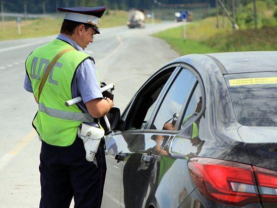 сотрудник ГИБДД проверяет автомобиль