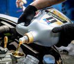 механик заливает масло в мотор